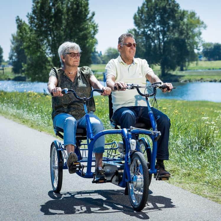Duofiets van Lintech. Man en vrouw genieten van fietstocht in de natuur.